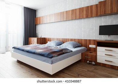 Modern bedroom in a wooden finish. Modern design decision bedroom apartments