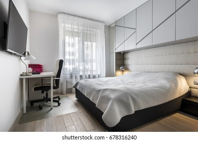 Modern bedroom with working space and small window
