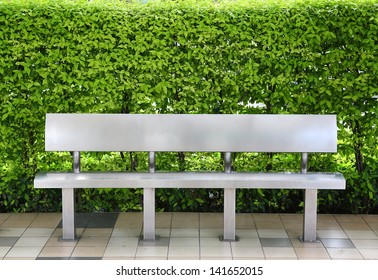Modern bench at bus stop against leaf wall