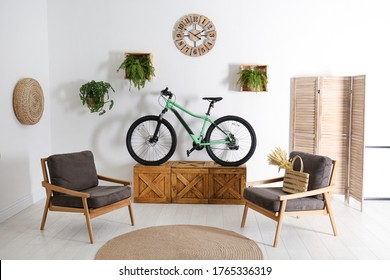 Modern bicycle and comfortable armchairs in stylish living room interior