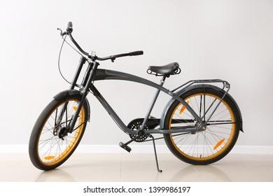 Modern bicycle near light wall