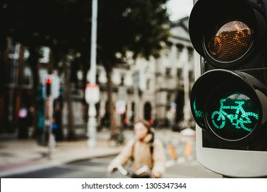 Modern bicycle traffic light glowing green with cyclist riding on street behind, Dublin