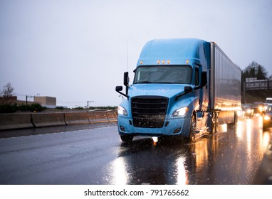 Modern big rig blue semi truck with covered semi trailer driving on twilight rainy wet highway with headlight traffic reflection of the rain drops