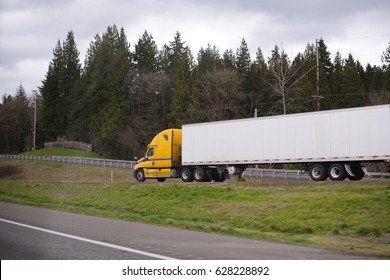 Modern big rig bright yellow semi truck for the long haul with long dry van trailer for dry cargo take exit the hill on the evergreen highway. Side view on professional truck.