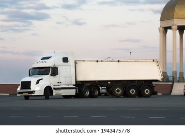 A modern big rig semi truck for long haulage with a high cabin for improving aerodynamic characteristics turns on the highway, transporting a dry van semi trailer with commercial cargo. Copy space