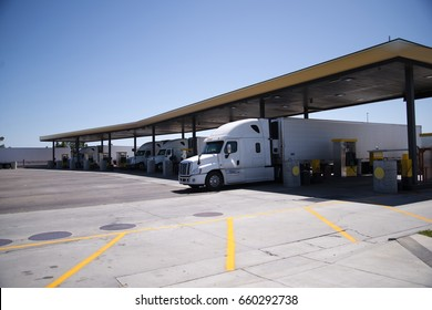 Modern big rigs semi trucks are standing in row at a long filling station with a canopy for refueling with diesel fuel for proceed delivering cargo to destination warehouse