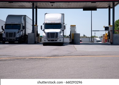 Modern big rigs white semi trucks are at a filling station with a canopy for refueling with diesel fuel