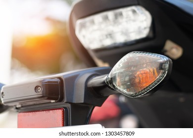 Modern bigbike motorcycle rear turn signal orange light. Road safety concept.