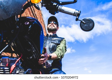Modern biker from bottom sits on classic motorcycle holding it and checking the industrial bricks buildings. Outdoor portrait and urban lifestyle