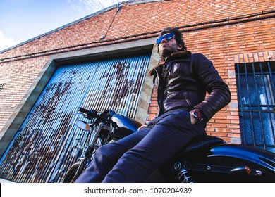 Modern biker sits on classic motorcycle holding it and checking the industrial bricks buildings. Outdoor portrait and urban lifestyle