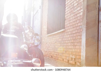 Modern biker sits on classic motorcycle looking at the sun durin