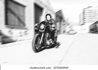 Modern biker speeds up motorcycle on a industrial street. Outdoor portrait and urban lifestyle