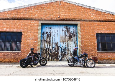 Modern bikers sits on classic motorcycle looking at the sun. Outdoor portrait and urban lifestyle