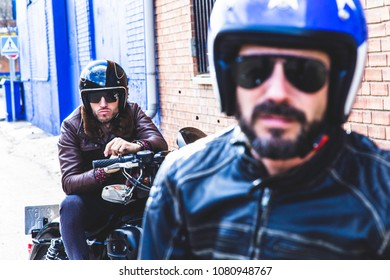 Modern bikers sits on classic motorcycle ready for photo shootin