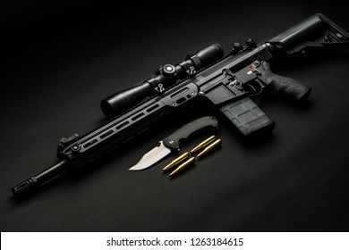 modern black automatic rifle with an optical sight lies on a dark background and next to the knife and ammunition