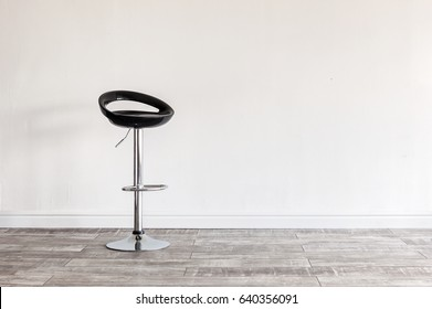 Modern black bar stool in front of wall with copyspace.