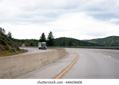 A modern black big rig semi truck with a dry van trailer carries industrial loads on a turn by a twisty split road in the mountain passes of California, climbing up the highway