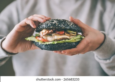Modern black burger in hands. Toned picture