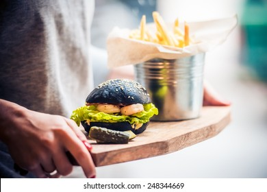 Modern black burger with squid ink buns and shrimps