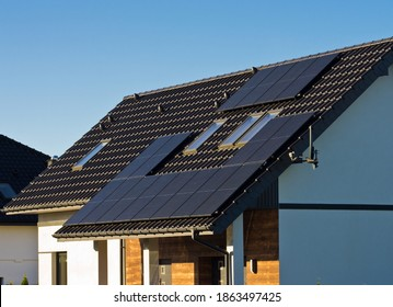 Modern black cells solar panels on the roof of private house arranged around attic windows. Renewable energy for home concept.