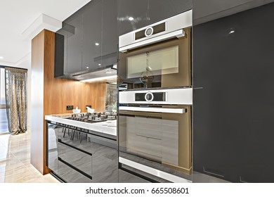 Modern black color pantry cupboards give a shiny look including attached ovens and stoves with a mirror beside, there is a curtain windows or door can be seen through the tiled hallway