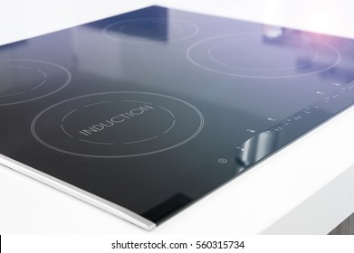 Modern black induction cooker on white countertop.