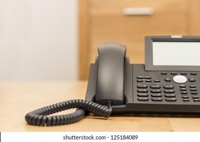 modernes schwarzes Telefon auf Holzschreibtisch mit unscharfem Hintergrund