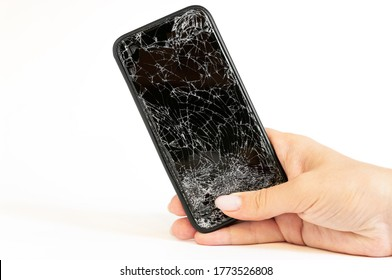 Modern black smartphone with highly broken screen in women hand on white background