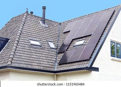 Modern black solar panels on roof of white house