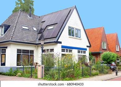 Modern black solar panels on roof of typical old Dutch house with garden flowers in suburban neighborhood street, Netherlands