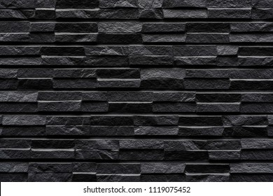 Modern black stone tile wall pattern and background