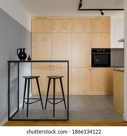 Modern, black table with tall bar stools in stylish kitchen with birch plywood cupboards - Shutterstock ID 1866134122