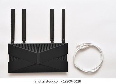 Modern black wi-fi 6 router on a white background with ethernet cable