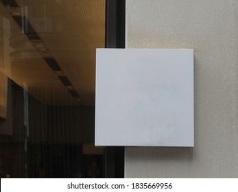 Modern blank generic sign outside a restaurant or retail store. White square block plaque for store logo. The store is in the background