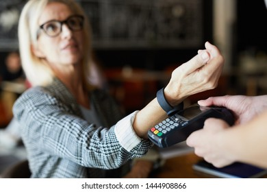 Modern blonde female keeping her wrist over electronic payment machine while paying for order through smartwatch in cafe