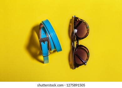 Modern blue belt and fashionable sunglasses in a black plastic frame lying isolated on white background. concept of summer attributes. free space for text