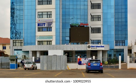 Modern blue building with Sahel-Sahara Bank and offices of Ghanaian companies. Computer Training Center. Insurance company. Pizza place. Urban landscape. Business in Ghana, Accra - January 21, 2017
