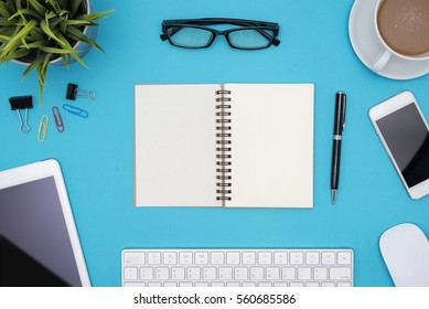 Modern blue office desk table with computer, tablet, other supplies, eye glasses and cup of coffee, Blank notebook page for input the text in the middle. Top view, flat lay.