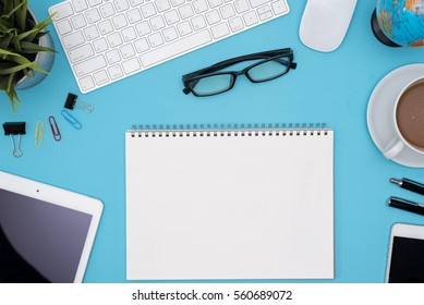 Modern blue office desk table with computer, tablet, cellphone, other supplies, eye glasses, cup of coffee and blank notebook page for input the text. Top view, flat lay.