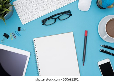 Modern blue office desk table with computer, tablet, cellphone, other supply, eye glasses, cup of coffee and blank notebook page for input the text. Top view, flat lay.