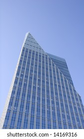 A modern blue office tower with a pointed top