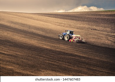 Modern blue tractor seeding after the harvest using gps and precision farming for navigation in the field. Agricultural pictures in Moravian Tuscany.