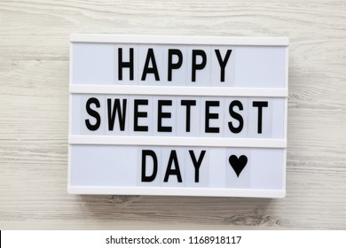 Modern board with text 'Happy Sweetest Day' word over white wooden surface, top view. From above, flat lay, overhead.