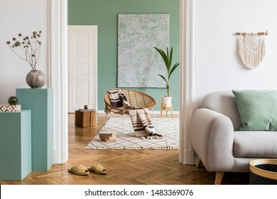 Modern and bohemian composition of interior design at apartment with gray sofa, rattan armchair, wooden cubes, plaid, tropical plant, macrame and elegant accessories. Stylish home decor. Template.