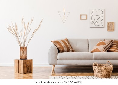 Modern boho interior of living room at cozy apartment with gray sofa, honey yellow pillows and plaid, mock up paintings, rattan basket and design personal accessories. Stylish home decor. Template. - Shutterstock ID 1444456808