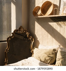 Modern boho style home interior design. Bohemian bedroom with bed, pillows, straw decorations, vintage retro mirror, concrete wall. Sunlight shadows on the wall. Hygge concept.