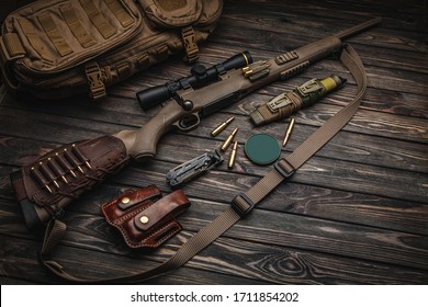 Modern bolted carbine and cartridges for it on a dark wooden table. Rifle with a telescopic sight on a dark background. Weapons for hunting, sports and self-defense. Postcard concept.