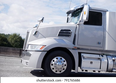 Modern bonnet professional light gray clean reliable new big rig day cab semi truck with big mirrors and aluminum steps and fuel tank running on the straight local road