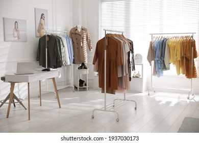 Modern boutique interior with stylish clothes and laptop