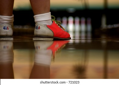 Modern bowling shoes have bright colors. A low angle shot right along the alley showing shoes and their reflection in the highly polished wood. Focus is on bowler's shoes